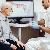 A dentist explaining how a denture works to a patient.
