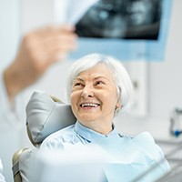An older woman smiling with a dentist.