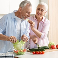 An older couple preparing a salad together.