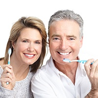 An older couple smiling and holding toothbrushes.