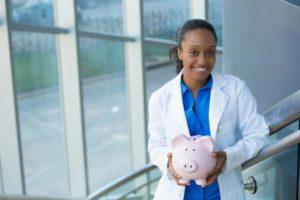dentist holding pink piggy bank