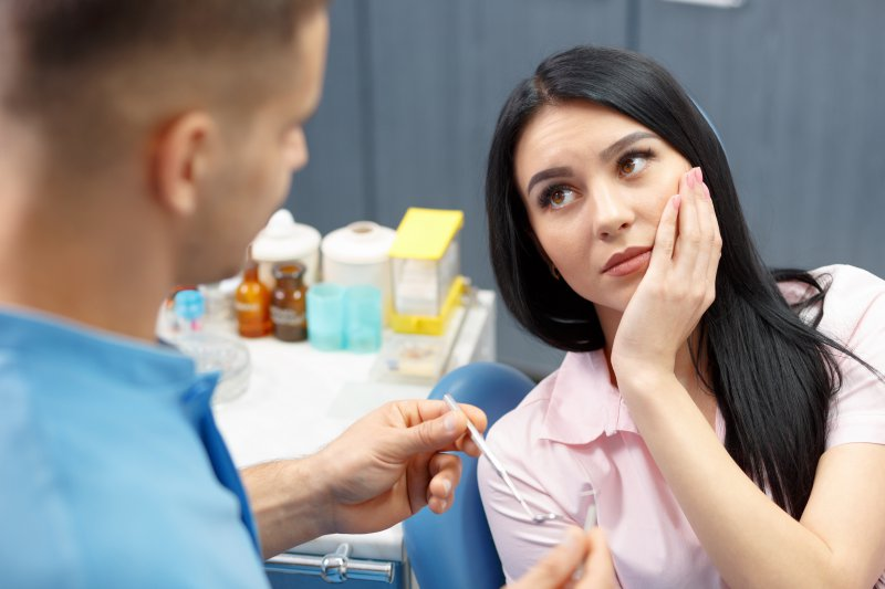 A woman with TMJ disorder listening to a dentist.